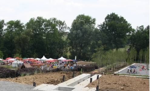 Im Vordergrund ist eine Baustelle zu sehen, im Hintergrund sind Pavillons und Sonnenschirme des Limesaktionstagessowie eine Sportfläche zu erkennen.