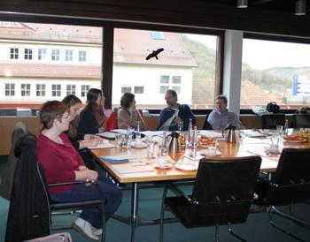 Teilnehmer der Agenda-Gruppe Limes sitzen an einem Tisch und beraten sich.
