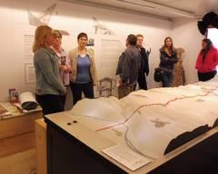 Sieben Personen stehen hinter einem Landschaftsmodell in einem Raum.