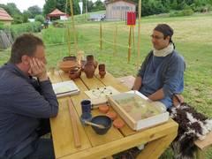 Zwei Teilnehmer der römischen Schautruppe aus Öhringen spielen ein Brettspiel.
