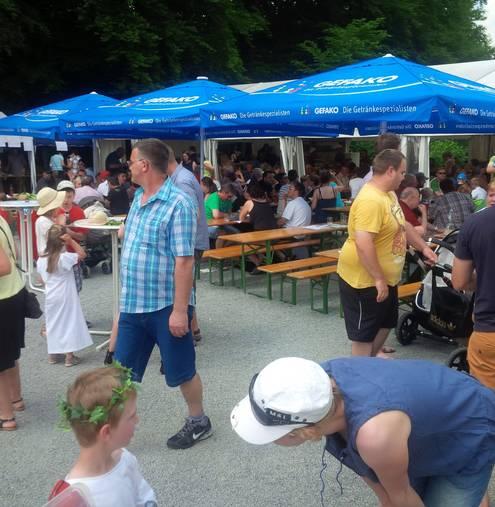 Eine größere Menge Menschens sitzt unter blauen Sonnenschirmen oder läuft umher.