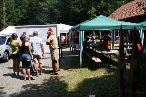 Rechts ist ein grüner Pavillon zu sehen, links stehen fünf Personen und betrachten eine Stellwand mit einem römischen Quiz.