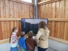Vier Personen stehen vor einem Bildschirm. Der ist Teil der Virtuellen Limeswelten.